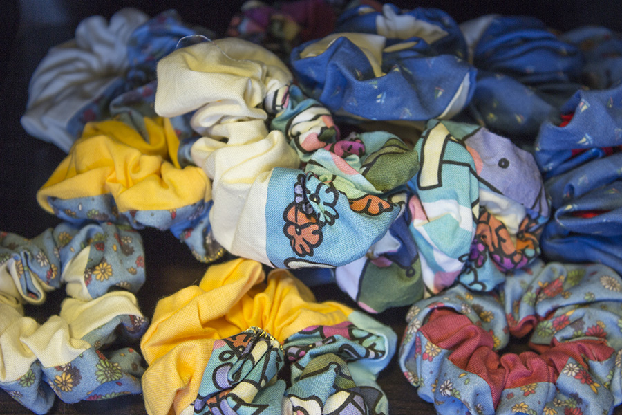 14 Scrunchies, all different combinations of printed fabric and solid colors and tags.